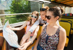 Group of smiling friends traveling by tour bus. Travel, tourism, summer vacation, sightseeing and people concept - group of smiling teenage friends in sunglasses Royalty Free Stock Photography