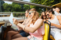 Group of smiling friends traveling by tour bus. Travel, tourism, summer vacation, sightseeing and people concept - group of smiling teenage friends in sunglasses Royalty Free Stock Photo
