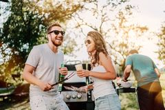 Group of smiling friends in vacation having beers and cooking on garden barbecue. Lifestyle, leisure concept stock photography