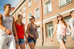 Group of smiling friends walking in the city Stock Images