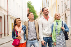 Group of smiling friends walking in the city. Friendship, travel and vacation concept - group of smiling friends walking in the city Royalty Free Stock Photo