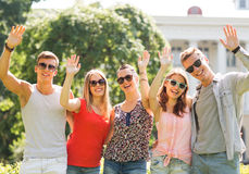 Group of smiling friends waving hands outdoors Stock Photo