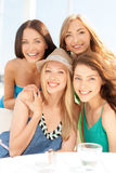 Group of smiling girls in cafe on the beach Stock Images
