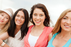 Group of smiling girls chilling on the beach Royalty Free Stock Image
