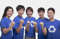 Group of smiling and happy people wearing recycling symbol t-shirts standing in a row with raised fists, studio shot Royalty Free Stock Photography