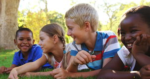 Group of smiling kids lying on grass