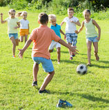 Group of smiling kids playing football together on green lawn in Royalty Free Stock Photography