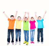 Group of smiling kids with raised hands. Group of smiling kids with raised hands in colorful t-shirts standing together - isolated on white Stock Image