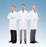 Group of smiling male doctors in white coats. Healthcare, profession, teamwork and medicine concept - group of smiling male doctors in white coats over blue stock photography