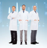 Group of smiling male doctors in white coats. Healthcare, profession, teamwork and medicine concept - group of smiling male doctors in white coats over blue stock image
