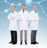 Group of smiling male doctors in white coats. Healthcare, profession, teamwork and medicine concept - group of smiling male doctors in white coats over blue royalty free stock image