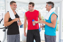 Group of smiling men talking each other. In fitness studio Royalty Free Stock Image