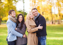 Group of smiling men and women in autumn park Stock Photo