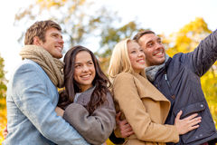 Group of smiling men and women in autumn park Royalty Free Stock Images