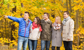 Group of smiling men and women in autumn park Stock Photos