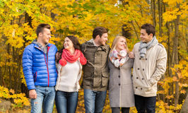 Group of smiling men and women in autumn park Royalty Free Stock Photo