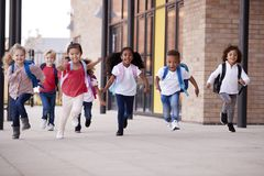 A group of smiling multi-ethnic school kids running in a walkway outside their infant school building after a lesson stock photos