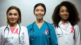 Group of smiling nurses with pink ribbons, breast cancer awareness, treatment stock photo