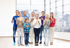 Group of smiling people applauding. Family, gender, generation and people concept - group of smiling men, women and boy applauding over empty office room or home Stock Photography