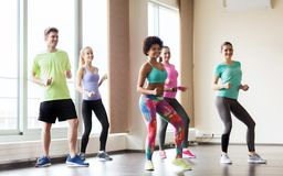 Group of smiling people dancing in gym or studio royalty free stock photo