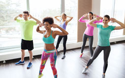 Group of smiling people dancing in gym or studio. Fitness, sport, dance and lifestyle concept - group of smiling people with coach dancing zumba in gym or studio Stock Photo