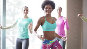 Group of smiling people dancing in gym or studio. Fitness, sport, dance and lifestyle concept - group of smiling women with coach dancing zumba in gym or studio stock footage