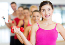 Group of smiling people with dumbbells in the gym Stock Images