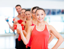 Group of smiling people with dumbbells in the gym Stock Photo