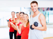 Group of smiling people with dumbbells in the gym Royalty Free Stock Photo
