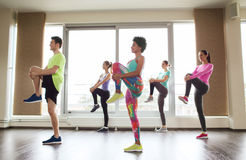 Group of smiling people exercising in gym Stock Images