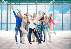 Group of smiling people having fun. Travel, vacation and people concept - group of happy people or big family having fun and waving hands over airport terminal Royalty Free Stock Photography