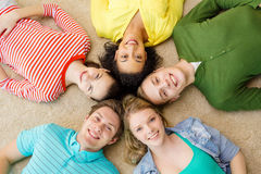 Group of smiling people lying down on floor Royalty Free Stock Image