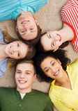 Group of smiling people lying down on floor. Education and happiness concept - group of young smiling people lying down on floor in circle Royalty Free Stock Image