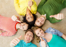 Group of smiling people lying down on floor. Education and happiness concept - group of young smiling people lying down on floor in circle and showing thumbs up Stock Photography