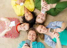 Group of smiling people lying down on floor. Education, technology and happiness concept - group of young smiling people lying down on floor in circle with Royalty Free Stock Photos