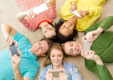 Group of smiling people lying down on floor. Education, technology and happiness concept - group of young smiling people lying down on floor in circle with Stock Images