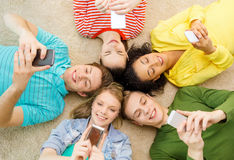 Group of smiling people lying down on floor. Education, technology and happiness concept - group of young smiling people lying down on floor in circle with Royalty Free Stock Images