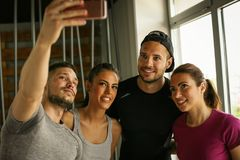 Group of smiling people making self-picture in gym. stock images