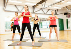 Group of smiling people meditating in the gym Stock Images