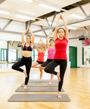 Group of smiling people meditating in the gym Stock Image