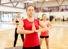 Group of smiling people meditating in the gym Royalty Free Stock Photo