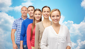 Group of smiling people over blue sky and clouds Royalty Free Stock Image