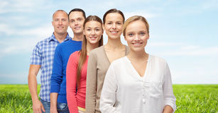 Group of smiling people over blue sky and grass Royalty Free Stock Photo
