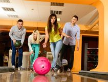 Group of smiling people playing bowling Stock Photos