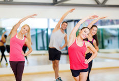 Group of smiling people stretching in the gym Stock Image