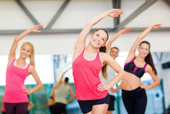 Group of smiling people stretching in the gym Royalty Free Stock Photos