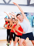 Group of smiling people stretching in the gym Stock Photos