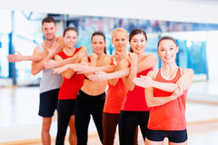 Group of smiling people stretching in the gym Stock Photo