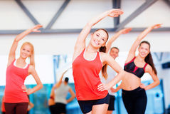 Group of smiling people stretching in the gym Royalty Free Stock Images
