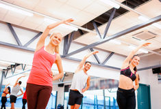 Group of smiling people stretching in the gym Stock Images